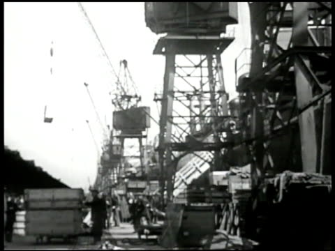 Crane in dock lifting cargo English dock workers WS Workers pushing carts full of bags CU Sign 'Britain Delivers The Goods' England import export...