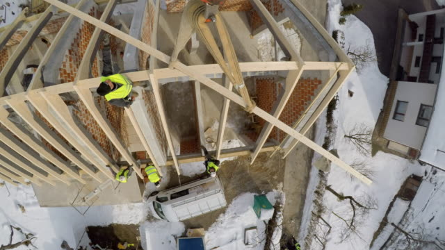 time-lapse pov crane lifting a wooden beam to the top of the house - crane shot stock videos & royalty-free footage