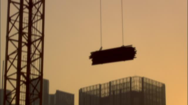 vídeos y material grabado en eventos de stock de ms, tu, crane lifting bundle of iron pipes on construction site, beijing, china - haz de luz