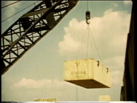 1941 MONTAGE Crane lifting large crate from train onto ship for distribution / United States