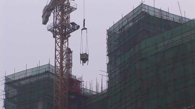vídeos y material grabado en eventos de stock de la ms crane lifting load to top of construction site/ beijing, china - grúa