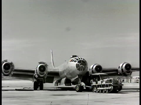 crane lifting men pushing engine cowling cover off b29 tractor pulling b29 on airfield field w/ few b29s parked some snow tractor backing up b29 on... - 1948 stock videos & royalty-free footage