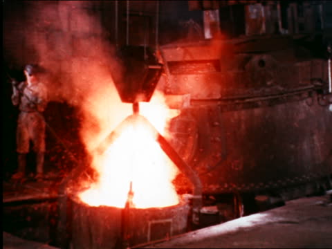 1946 crane lifting vat of molten metal in factory / industrial