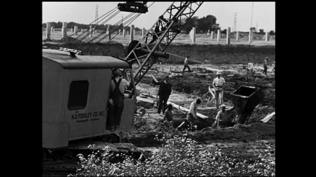 crane lifting wet cement into ditch at construction site; workers standing in the field watching - 1940 1949 stock-videos und b-roll-filmmaterial