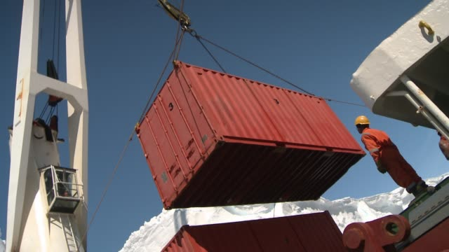 a crane lifts a giant metal container toward a cargo ship. available in hd. - pulley stock videos & royalty-free footage