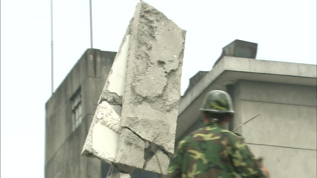 A crane lifts a slab of concrete from a collapsed building in the aftermath of the 2008 Sichuan earthquake