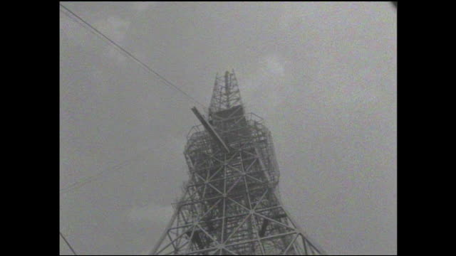 A crane lifts an exostructure girder toward its assembly position on the Tokyo Tower.