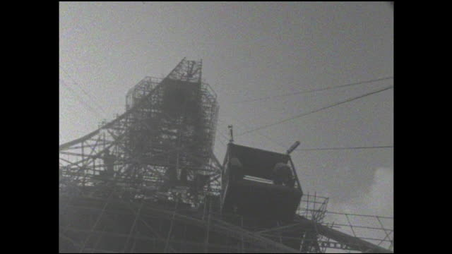 a crane lifts construction workers on a platform as other workers walk on scaffolds at the tokyo tower construction site. - letterbox format stock videos & royalty-free footage