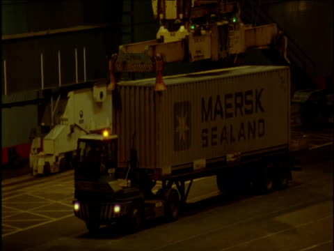 crane lifts container from lorry at cargo port at night felixstowe - 積荷を降ろす点の映像素材/bロール