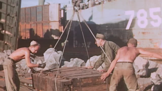 crane lowering ammunition crates on pallet us marines unhooking pallet and pushing it along tracks into lst782 during world war ii pacific campaign - ammunition stock videos & royalty-free footage