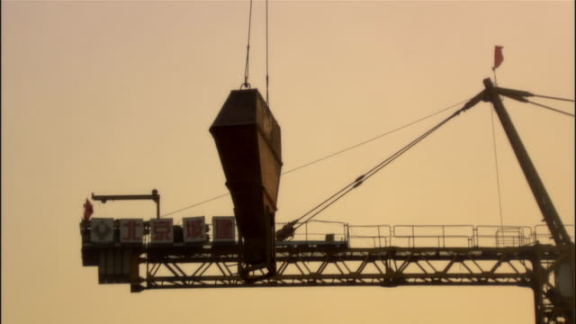 MS, TD, Crane lowering metal girder on construction site, Beijing, China