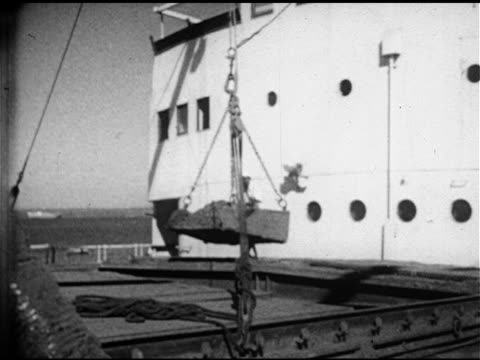 crane lowering open container of ore onto ship indian men working crane unhooking container bed chain dumping container into cargo hold inexpensive... - 1953 stock videos and b-roll footage