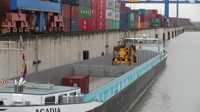 A crane lowers a shipping container into a barge moored at Duisport DITTerminal operated by Duisburger Hafen AG in Duisburg Germany on Thursday Feb 1...