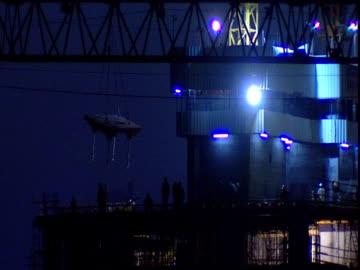 crane lowers above building site men work below dubai - crane construction machinery stock videos & royalty-free footage