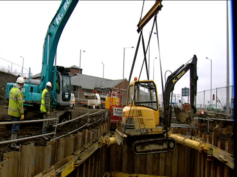 crane lowers mini mechanical digger into deep pit on building site - condition stock videos & royalty-free footage