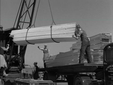 A crane moves a consignment of timber onto a truck