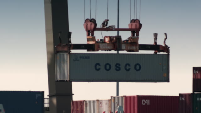 a crane moves a large shipping container and places it on board a cargo ship. - picking up stock videos and b-roll footage