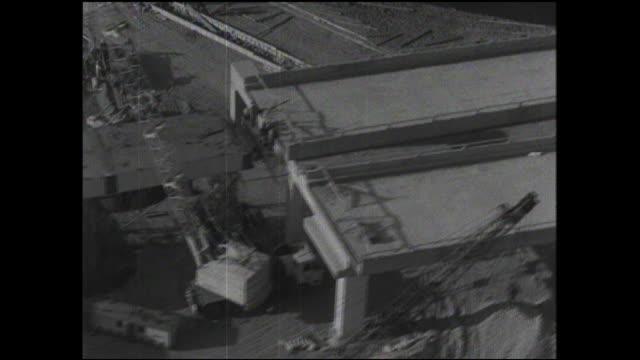 a crane moves a steel girder on a tokyo metropolitan expressway construction site overpass. - 建物の骨組み点の映像素材/bロール