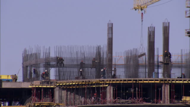 A crane moves materials around a construction site in Astana Kazakhstan. Available in HD.