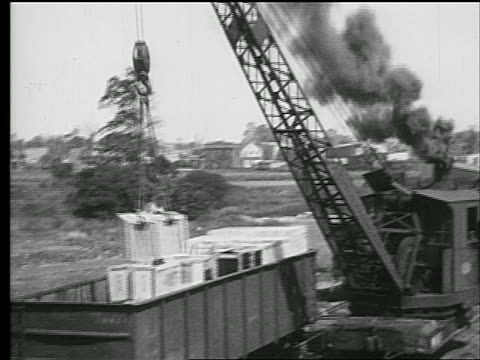 b/w 1927 pan crane moving large crate into freight car where man assists / industrial - crane stock videos & royalty-free footage