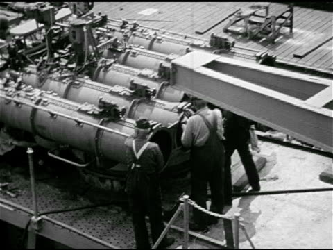 vídeos de stock, filmes e b-roll de crane moving naval torpedo tubes ha td ws men cleaning mounted torpedo tubes on deck of us navy ship tu vs crane holding turning turret cannons in... - 1943
