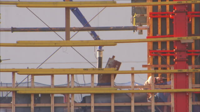 a crane operates near a construction worker and scaffolding. - scaffolding stock videos & royalty-free footage