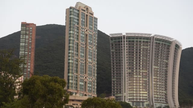 A crane operates next to residential buildings in the Mid Levels area of Hong Kong China on Friday Nov 27 Residential buildings stand in the...