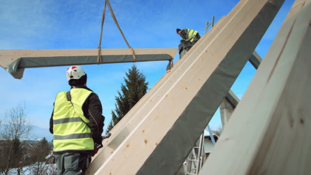 crane operator standing on the roof and controlling the crane to put a wooden beam into place - costruire video stock e b–roll