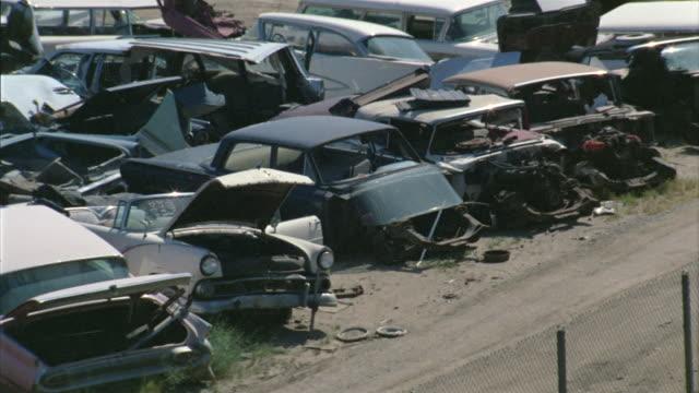 1963 MONTAGE Crane picking up car in junkyard / Sun Valley, California