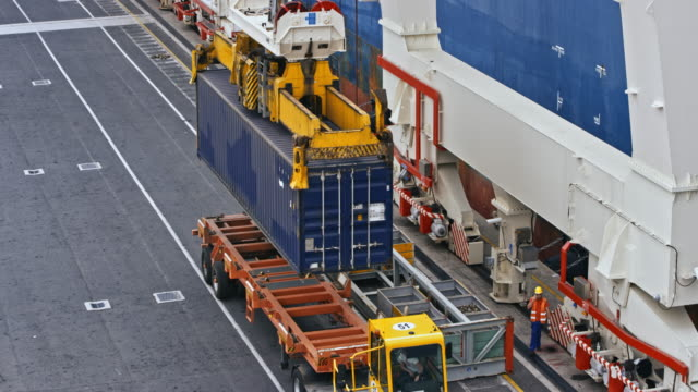 crane placing a shipping container onto a truck at the container terminal - unloading stock videos & royalty-free footage
