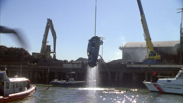 a crane salvages a car as coast guard vessels provide security. - wrack stock-videos und b-roll-filmmaterial