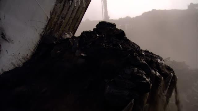 a crane scoops up coal from a construction truck and dumps it. - ausschöpfen stock-videos und b-roll-filmmaterial