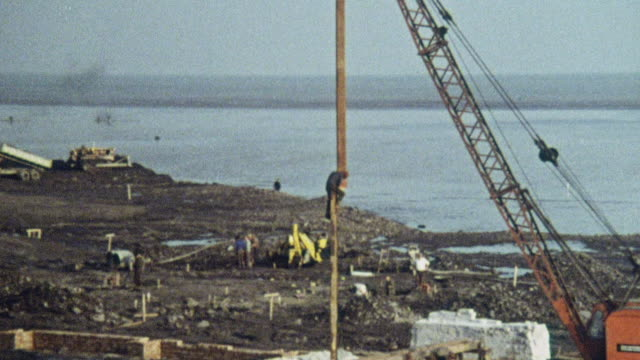 1969 montage crane setting vertical risers in place during building of the hoverport at pegwell bay / ramsgate, kent, england - ramsgate video stock e b–roll