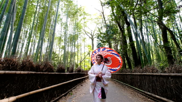 4 k クレーン ショット: アジアの女性の伝統的な着物衣装で嵐山・嵯峨野の竹林を歩いて、京都市、日本 - は日本にあなたを歓迎 - 竹点の映像素材/bロール