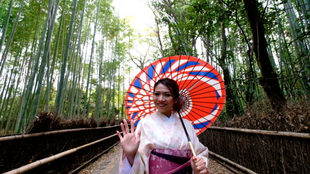 4k crane shot : a asian woman in traditional kimono costume with japanese rickshaw at bamboo forest at arashiyama and sagano, kyoto,japan - welcomes you to japan - japan stock videos & royalty-free footage