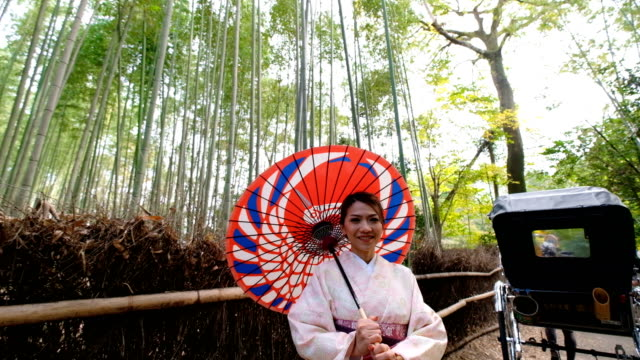 4k crane shot : a asian woman in traditional kimono costume with japanese rickshaw at bamboo forest at arashiyama and sagano, kyoto,japan - welcomes you to japan - risciò video stock e b–roll