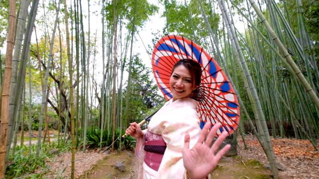 4k crane shot : a asian woman in traditional kimono costume with japanese rickshaw at bamboo forest at arashiyama and sagano, kyoto,japan - welcomes you to japan - kimono stock videos and b-roll footage