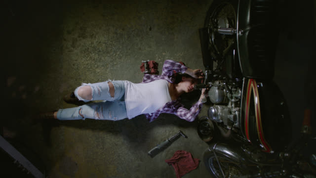 Crane shot. Camera moves down on female mechanic ratcheting under motorcycle on garage floor.