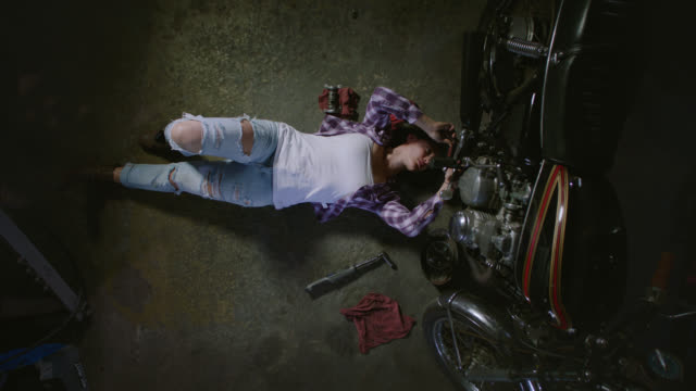 Crane shot. Camera moves up as female mechanic on back ratchets under motorcycle on garage floor.
