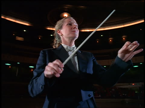 crane shot female conductor conducting in empty concert hall - conductor stock videos & royalty-free footage
