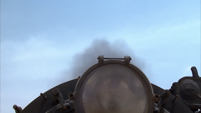 crane shot from low angle view of headlight of locomotive train traveling through desert to overhead view of steam billowing from stack / egypt - crane shot stock videos & royalty-free footage