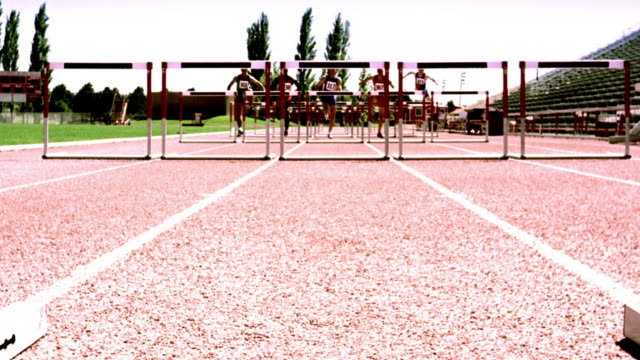 overexposed selective focus crane shot group of men jumping hurdles in race on track - ライクラ点の映像素材/bロール