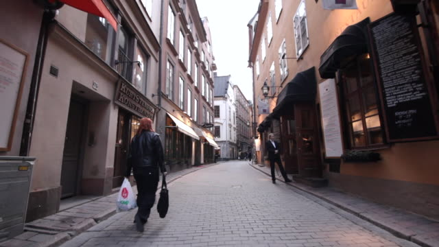 crane shot of a person walking along a narrow street in gamla stan, stockholm. - narrow stock videos and b-roll footage