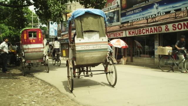 Crane shot of a rickshaw as it pulls away into a street in Guwahati in Assam, India.