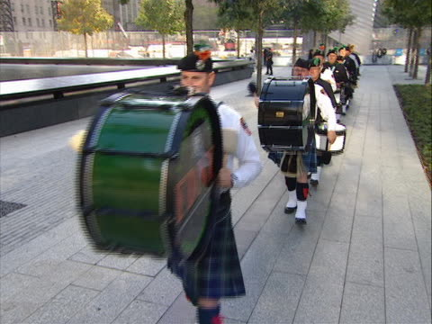 crane shot of bag pipers walking to play at the september 11th memorial ceremony on 9/11/11, the tenth anniversary of the attacks. president obama... - anniversary stock videos & royalty-free footage