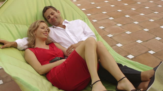 crane shot of couple relaxing in hammock together/marbella region, spain - crane shot stock videos and b-roll footage