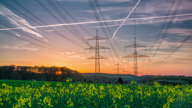 Crane Shot of Electricity Pylons On Field Against Sky During Sunset