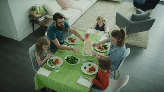 vídeos de stock e filmes b-roll de crane shot of family offering bread to children at dinner table / lehi, utah, united states - lehi