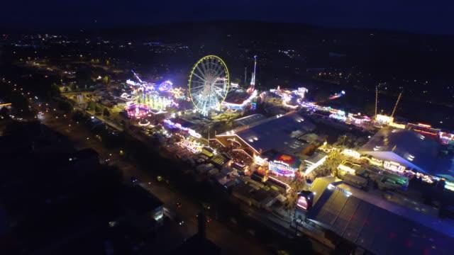 Crane shot of illuminated amusement park in city at night