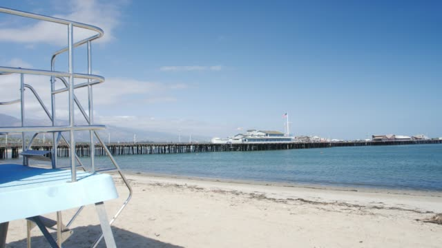 Crane shot of Stearns Wharf Pier and life guard post from beach, Santa Barbara, California, United States, North America